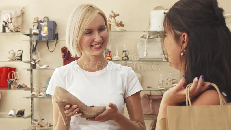 Shop assistant showing shoes to customer stock image