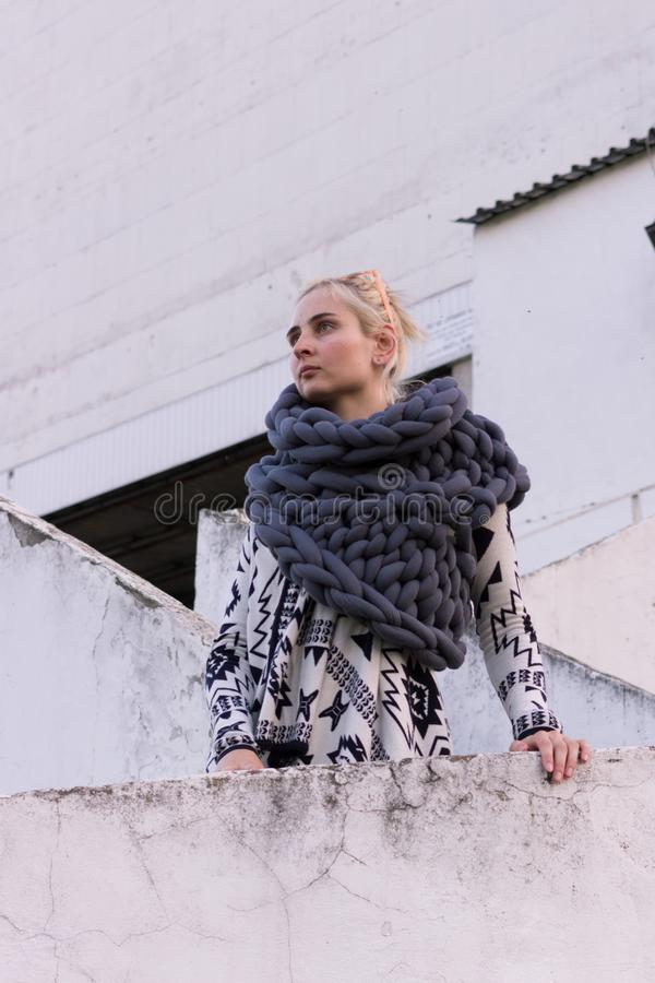 Blonde young beautiful fashion girl wearing aztec black and white jacket and knitted grey vest scarf. Festival outfit royalty free stock image