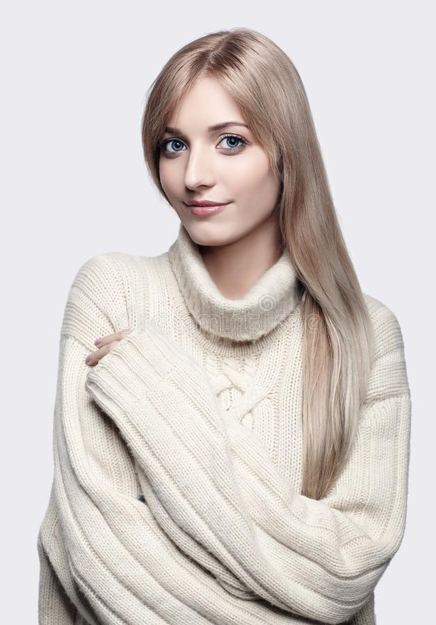 Blonde woman in cashmere sweater. Blonde young beautiful woman dressed in large white cashmere sweater on gray background stock images