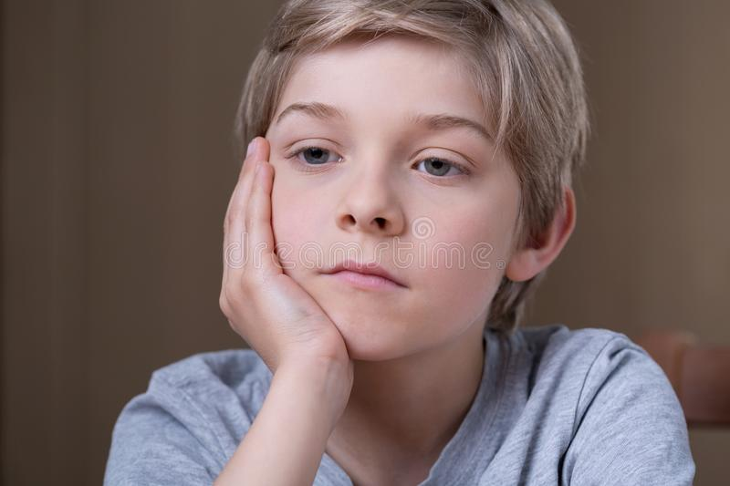 Blonde young boy thinking stock photos