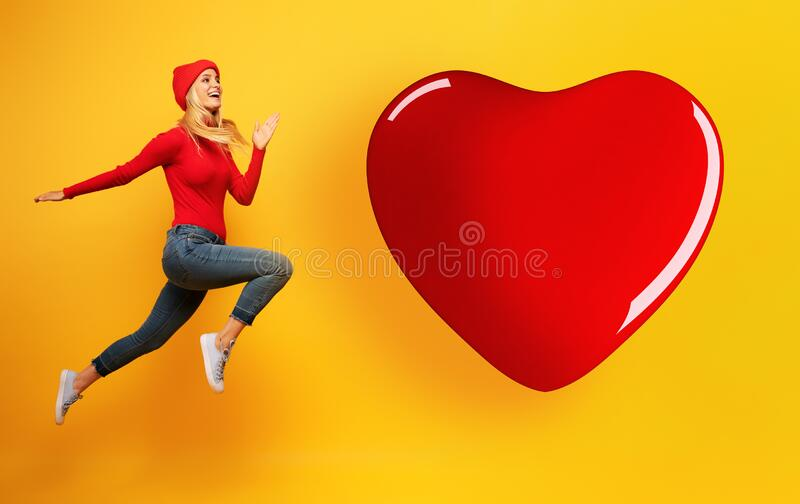 Blonde young girl jumps to reach a big heart. Concept of relationship, meeting on social network stock image