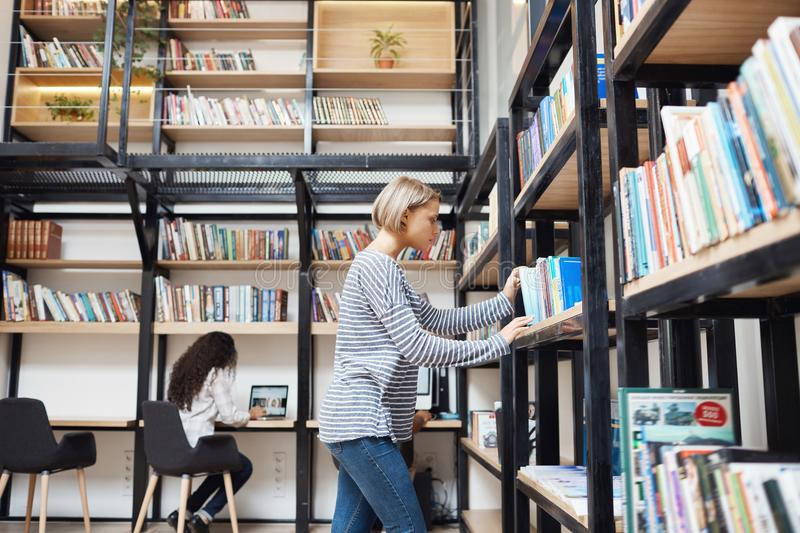 Blonde young good-looking girl in striped shirt and jeans searching for a book on shelf in library, getting ready for stock photos