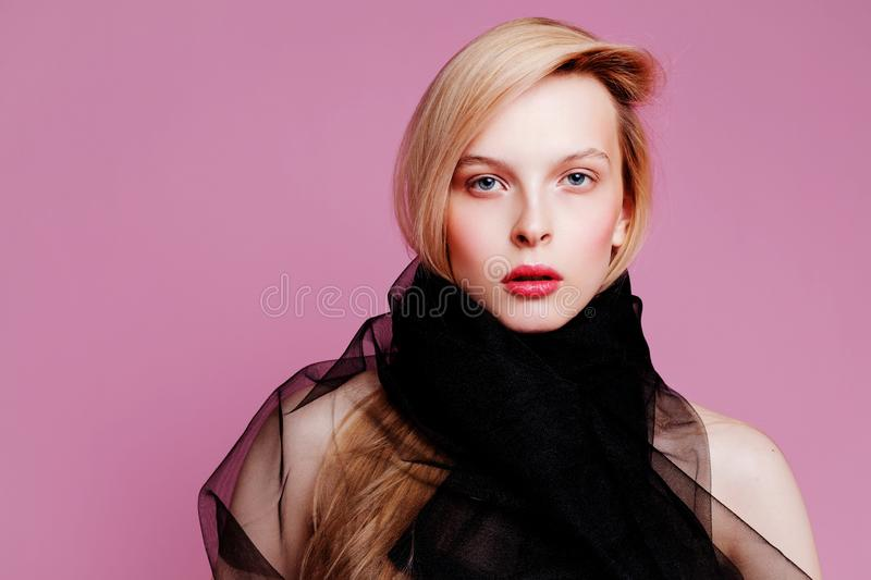 Blonde young woman in elegant body. Girl posing on a pink background. Make -up and hairstyle. Fashion photo royalty free stock photos
