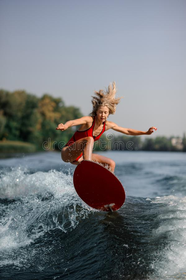 Blonde woman jumping on a wakeboard on the blue water. Blonde young woman jumping on a wakeboard on blue water on warm and sunny day royalty free stock photo