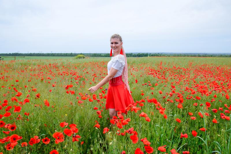 Blonde young woman in red skirt and white shirt, red earrings is in the middle of a poppy field royalty free stock photo
