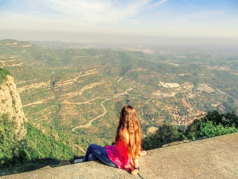 Blonde young woman sits on a viewing platform and looks down at Montserrat Mountain valley in Catalonia Spain, view from the royalty free stock photos