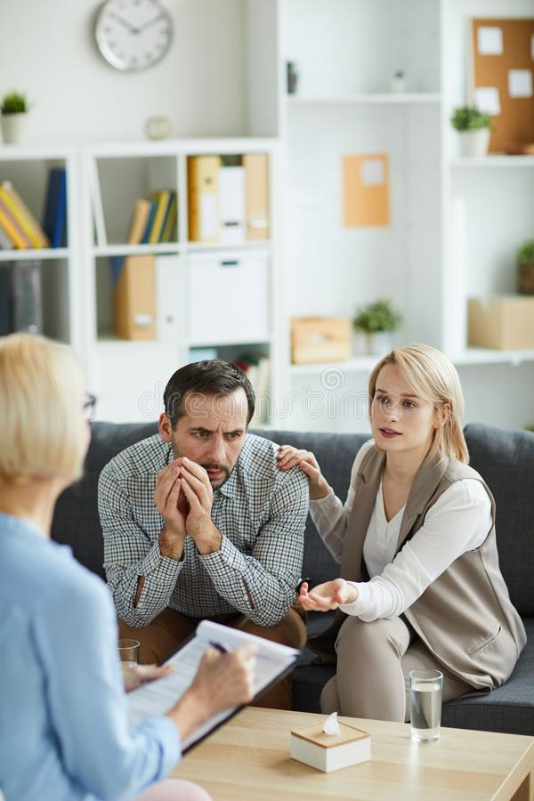 Asking for advice. Blonde young women explaining something to counselor while sitting on couch next to her husband stock photo