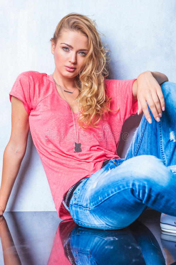 Blonde young women wearing pink shirt while posing for the camer stock photos