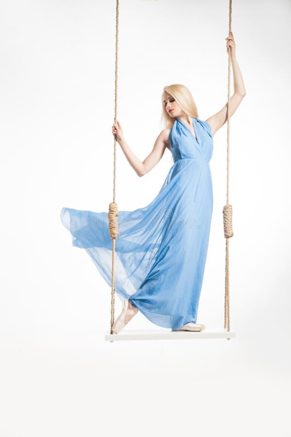 Blondeballerina in blauwe kleding op schommeling stock foto's