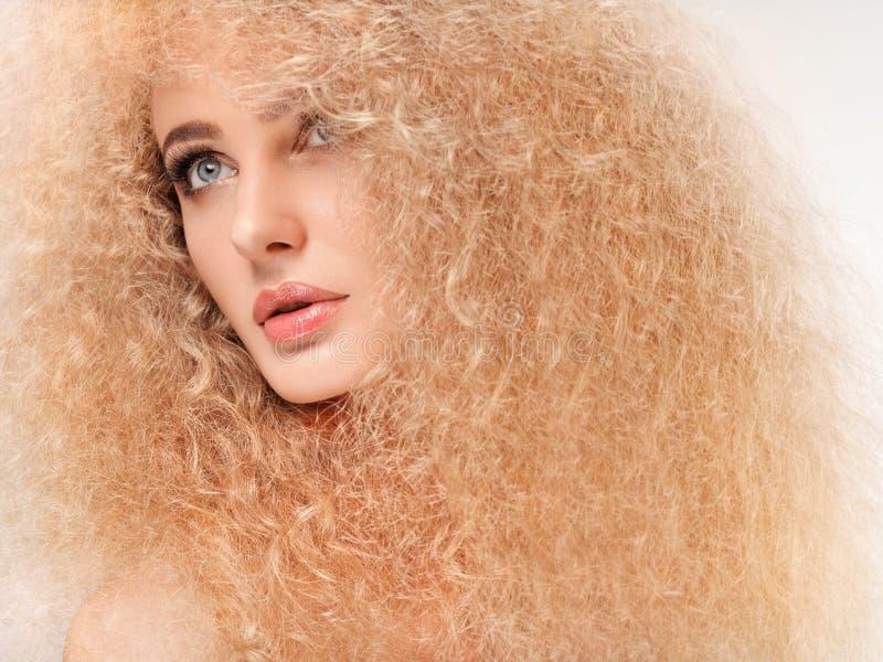 Blondehaar. Mooie Vrouw met Krullend Lang Haar. Hoog - kwaliteit stock fotografie