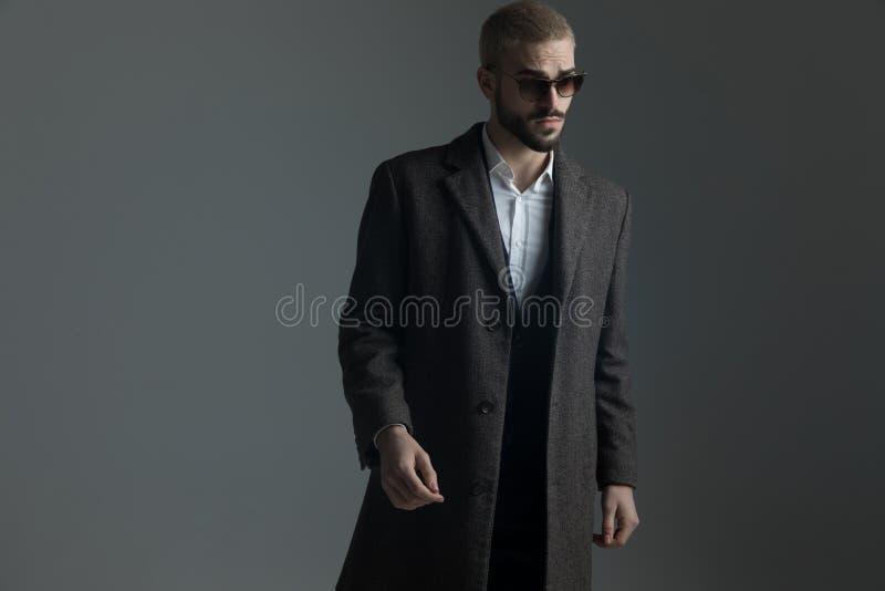 Blondekerel in kostuum met zonnebril en longcoat het warlking stock afbeelding