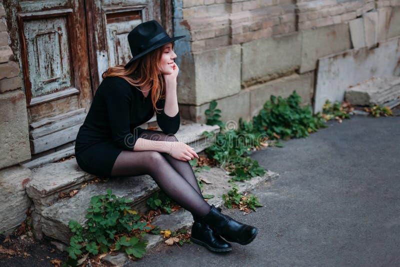 Blondel som ler flickan med långt hår, i svart klänning i hatt, sitter på momenten på den gamla bakgrunden av tappningantikvitete royaltyfri foto