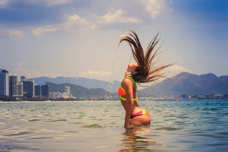 Blondemeisje in bikinitribunes in overzees geschud hoofdliftenhaar omhoog royalty-vrije stock afbeeldingen