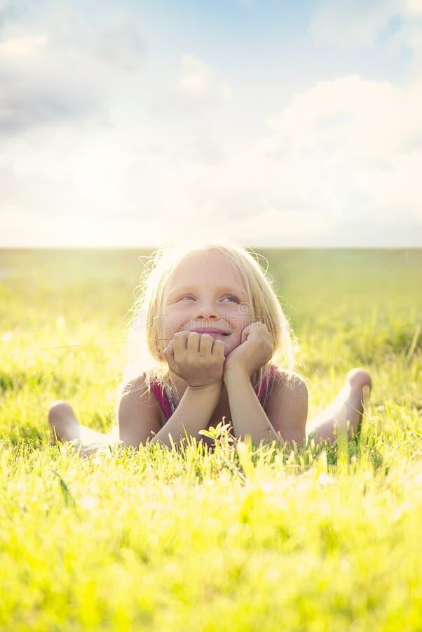 Blondemeisje dat en op het gras bij de zomerzonsondergang glimlacht ligt die de hemel bekijkt Natuurlijke geluk, pret en harmonie royalty-vrije stock afbeelding