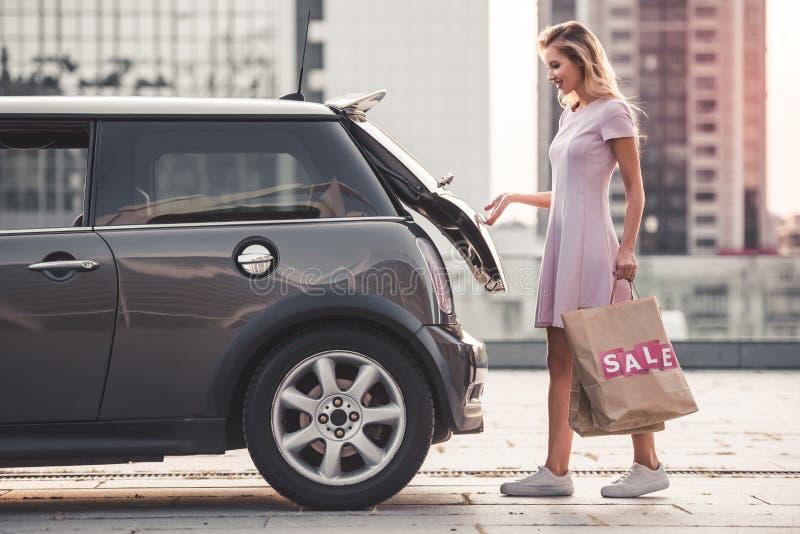 Blondemeisje dichtbij de auto stock afbeelding
