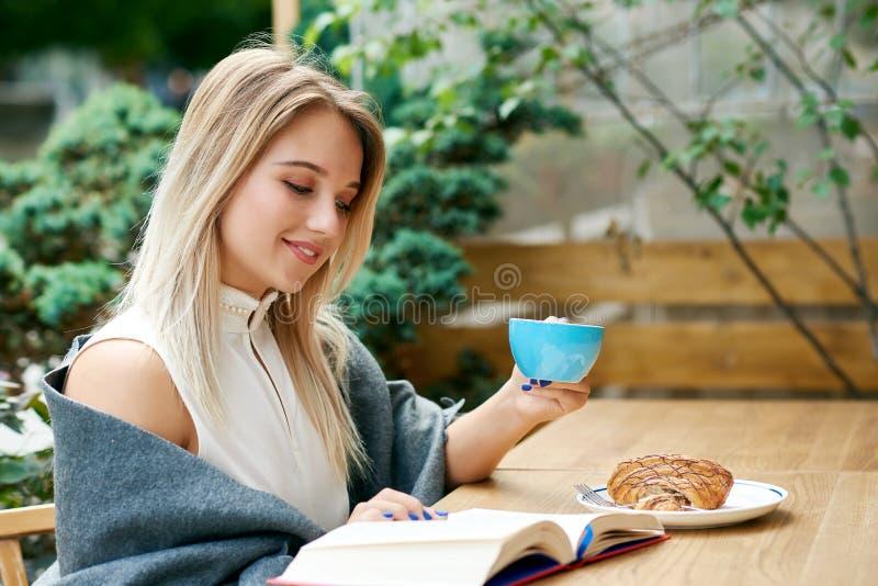 Blondemeisje die een boek lezen terwijl in openlucht het drinken van koffie op koffie` s zitkamer stock afbeeldingen