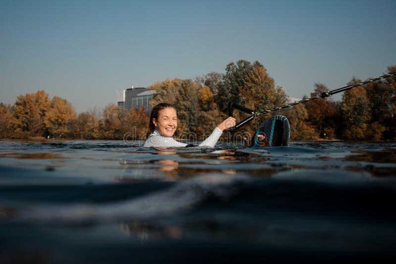 Blondemeisje die een wakeboard in de rivier houden stock foto's