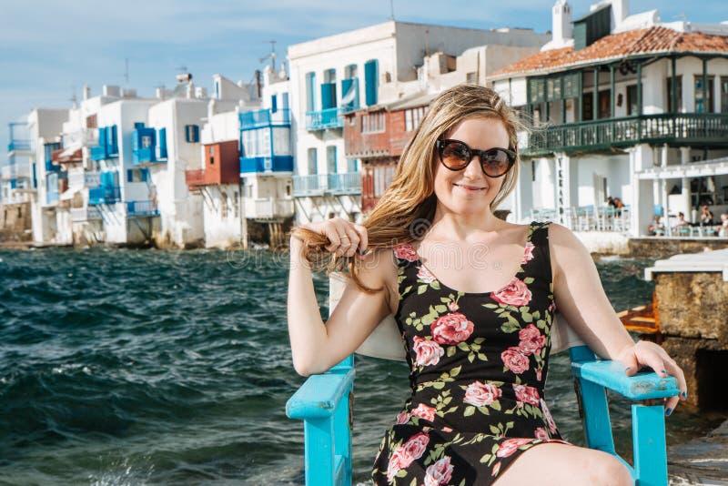 Blondemeisje die met zonnebril op een stoel bij het strand zitten stock afbeeldingen