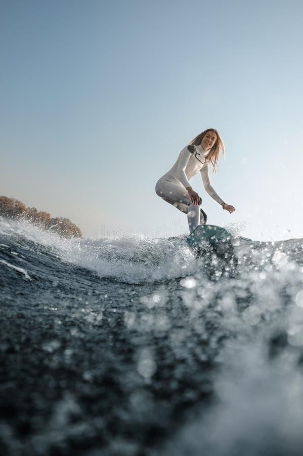 Blondemeisje die op wakeboard op de rivier berijden stock foto's