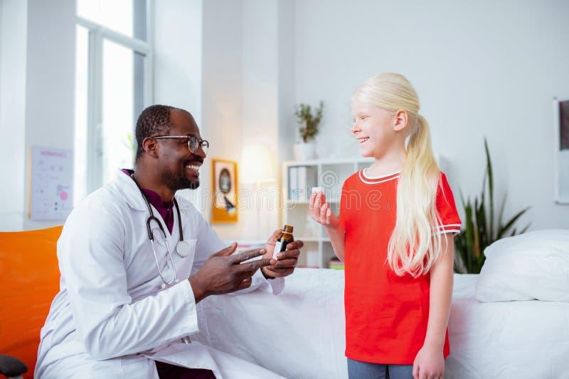 Blondemeisje die terwijl het drinken van de bezoekende pediater van de hoeststroop glimlachen stock afbeeldingen