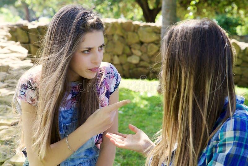 Blondemeisje die vinger boos met meisje richten royalty-vrije stock fotografie