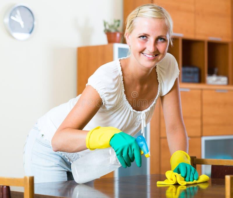 Blondemeisje die in woonkamer bestrooien stock foto's