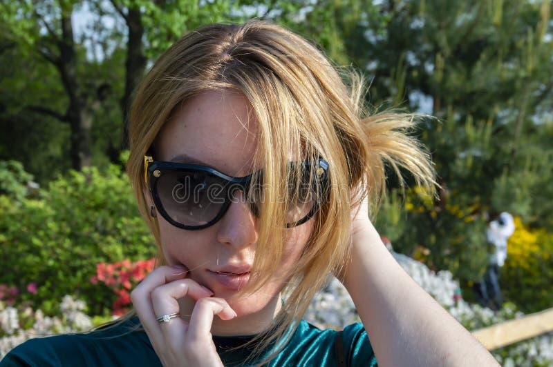 Blondemeisje in donkere zonnebril in de zon stock foto