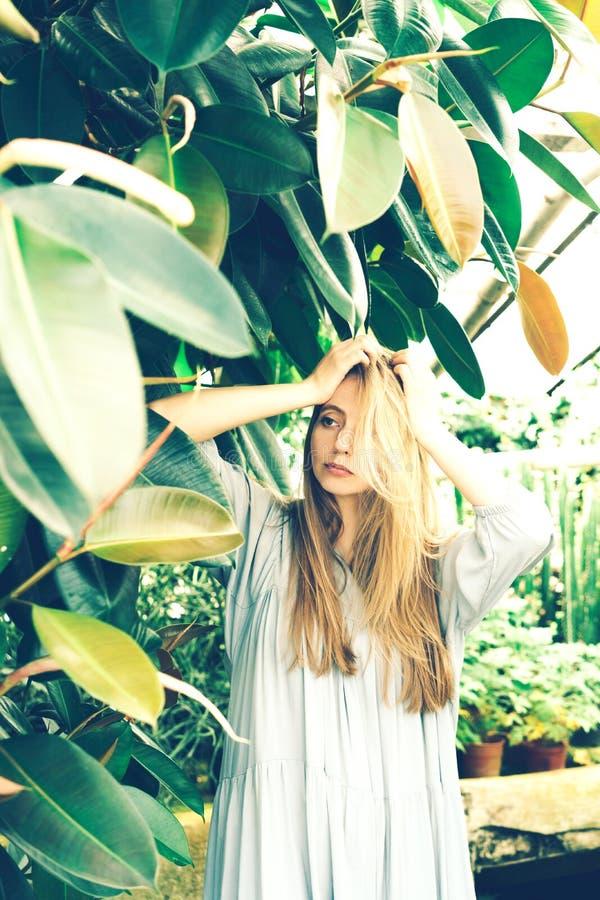 Blondemeisje in een tropische struik in de serre stock fotografie