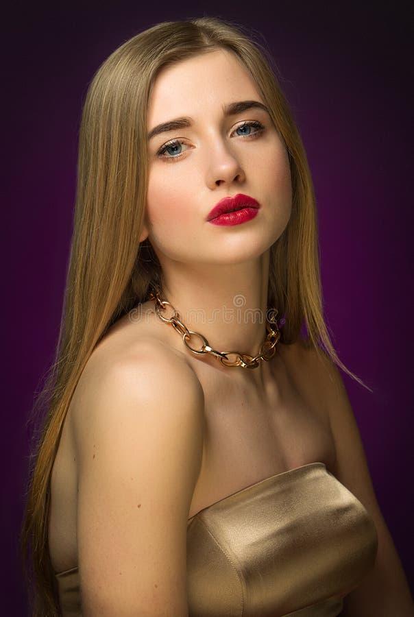 Blondemeisje in goud Klassiek portret Blauwe ogen en rode lippen stock afbeeldingen