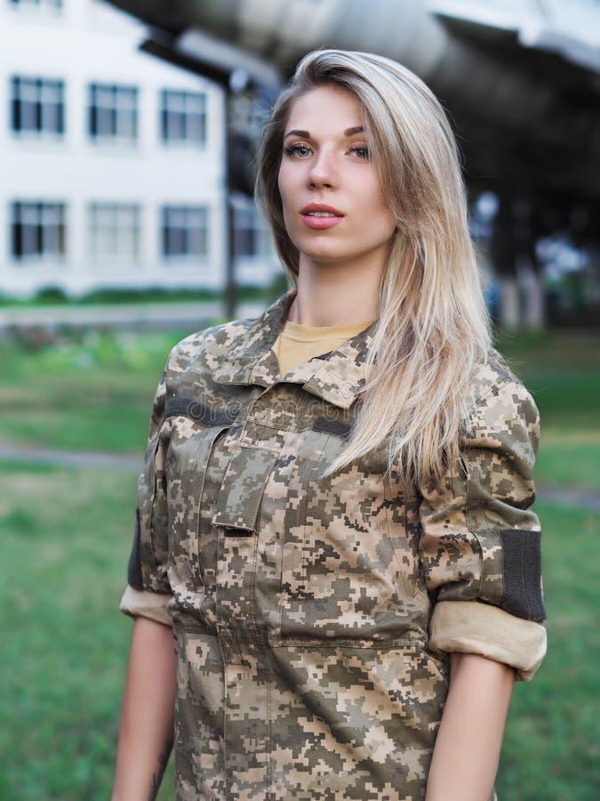 Blondemeisje in het militaire eenvormige blijven dichtbij het vliegtuigportret stock afbeeldingen