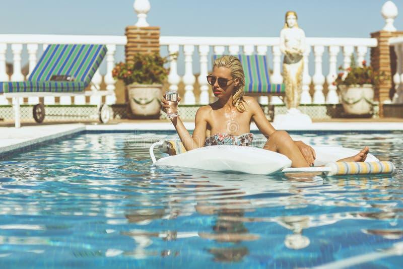 Blondemeisje het ontspannen in pool stock afbeelding