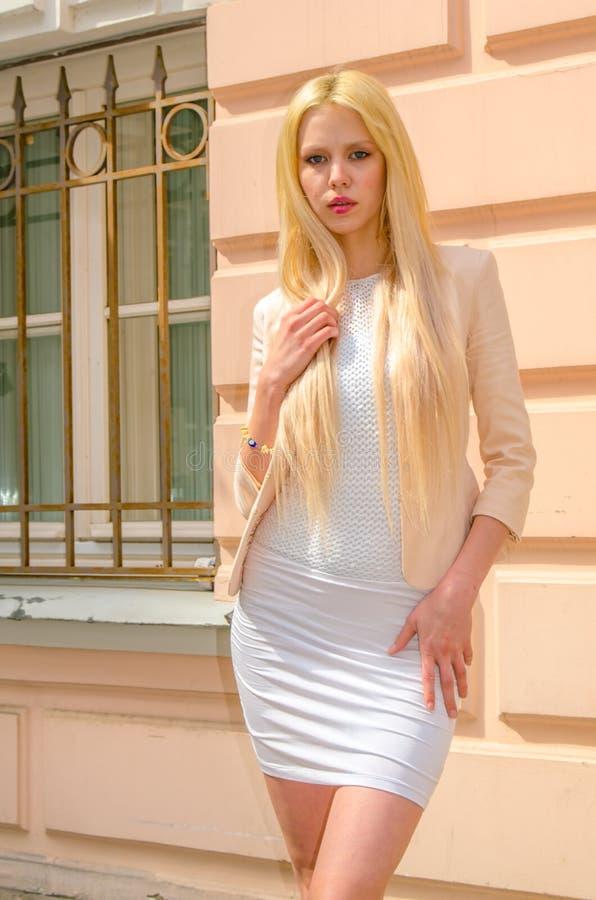 Blondemeisje in het witte kleding stellen op de straat van de oude stad stock fotografie