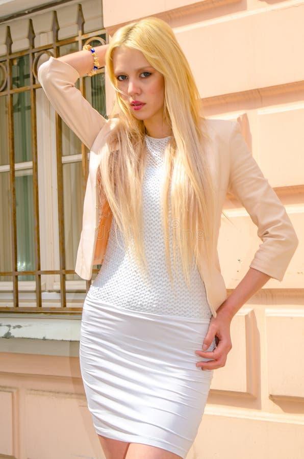 Blondemeisje in het witte kleding stellen op de straat van de oude stad stock foto's
