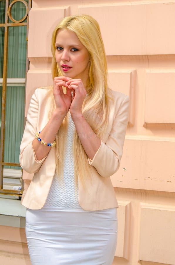 Blondemeisje in het witte kleding stellen op de straat van de oude stad royalty-vrije stock foto