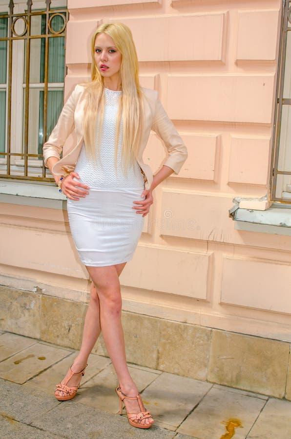 Blondemeisje in het witte kleding stellen op de straat van de oude stad royalty-vrije stock afbeelding