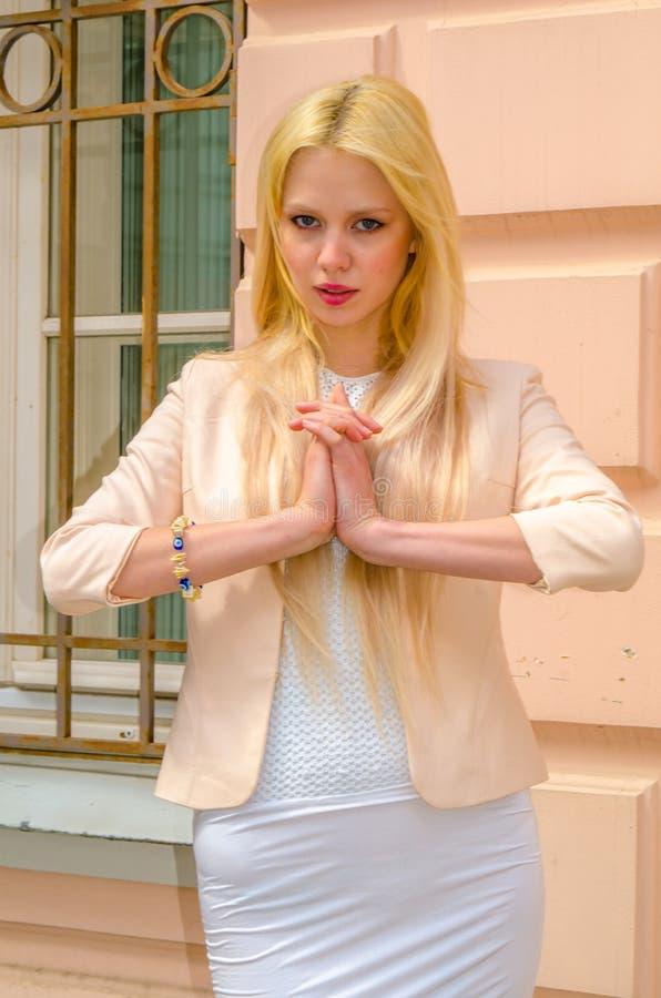 Blondemeisje in het witte kleding stellen op de straat van de oude stad royalty-vrije stock fotografie