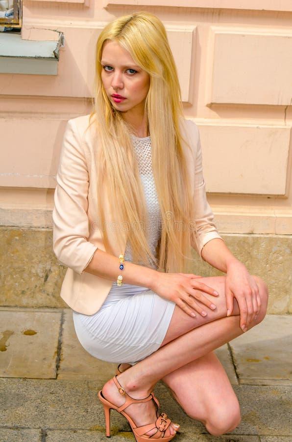 Blondemeisje in het witte kleding stellen op de straat van de oude stad royalty-vrije stock afbeeldingen