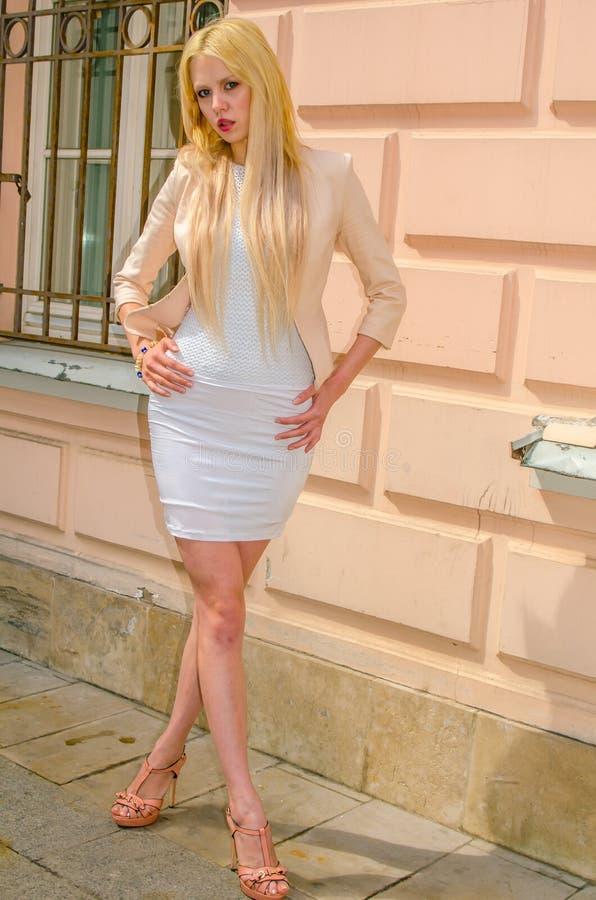 Blondemeisje in het witte kleding stellen op de straat van de oude stad royalty-vrije stock foto's
