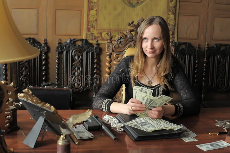 Blondemeisje met dollars in haar handen en pistolen stock foto
