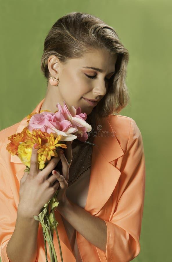 Blondemeisje met in oranje holdingsbloemen, stock foto's
