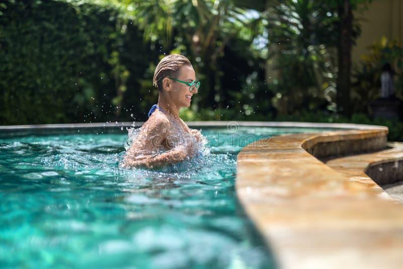 Blondemeisje in pool stock afbeelding