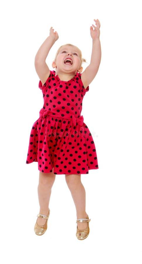 Blondemeisje in sprongen van een de rode stipkleding stock foto