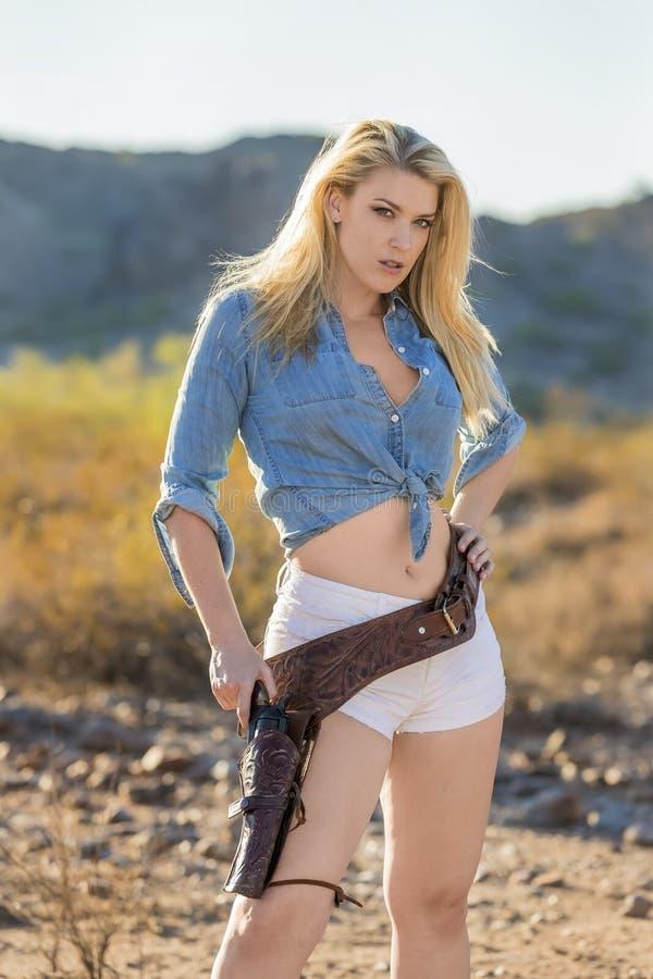 Blondemodel in Woestijn met Kanon stock foto's