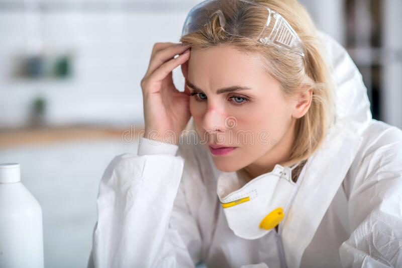 Blondenvrouw in witte werkkleding die er moe uitziet royalty-vrije stock foto's