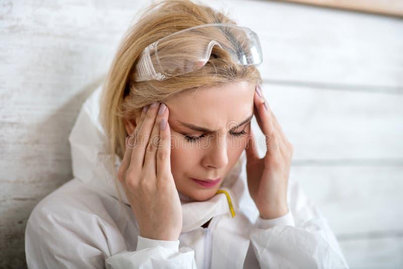 Blondenvrouw in witte werkkleding met hoofdpijn royalty-vrije stock fotografie