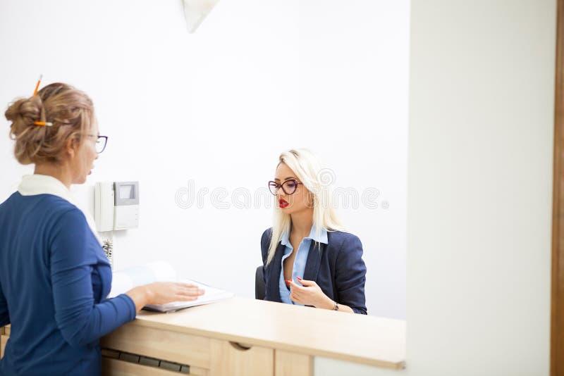 Blondeonderneemster die aan haar blondesecretaresse spreken stock fotografie