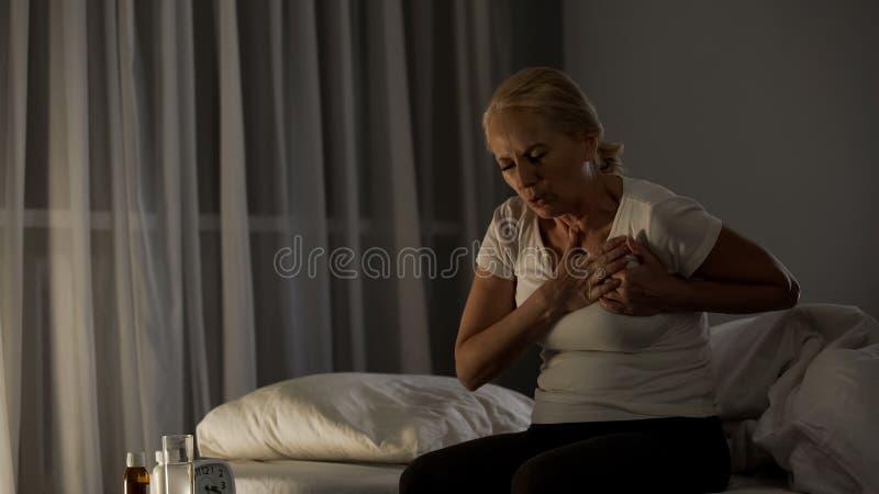 Blonder älterer weiblicher rührender Kasten, glaubende scharfe Schmerz, Herzkrankheitsinfarkt lizenzfreie stockbilder
