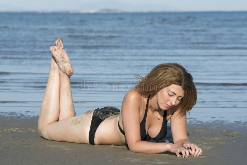 Blonder Frauenabnutzungsschwarzbikini, der auf dem Strand liegt stockfoto