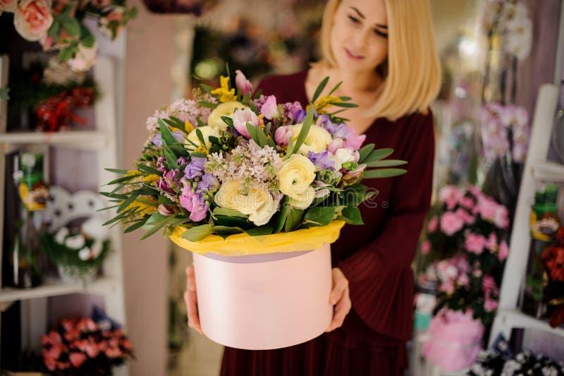 Blonder Frauenholding-Hutkasten mit Blumen lizenzfreies stockfoto