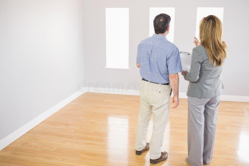 Blonder Grundstücksmakler, der einem möglichen Käufer einen Raum zeigt lizenzfreies stockbild